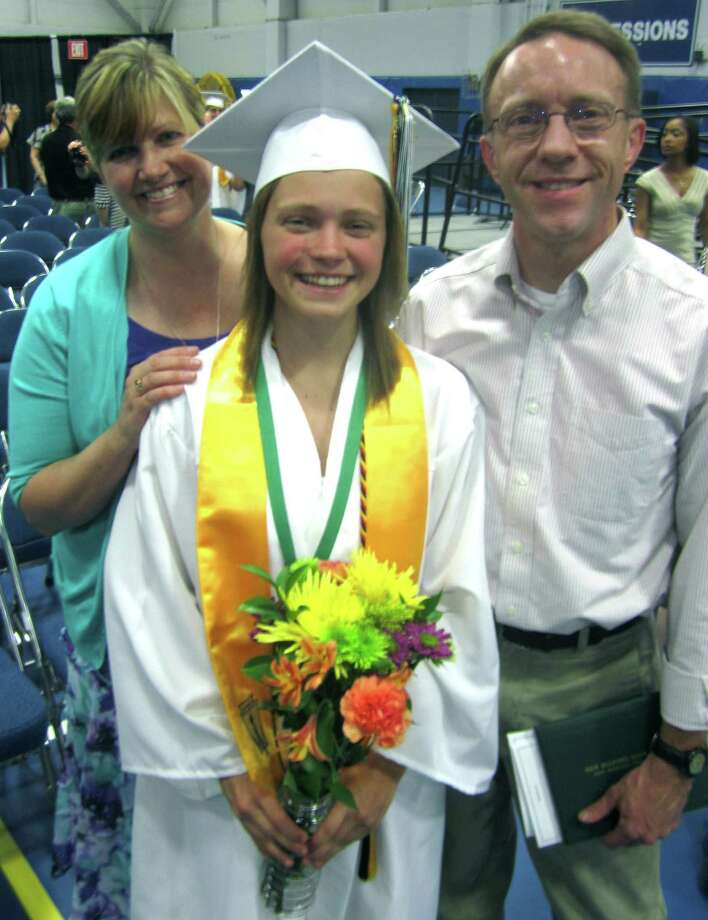 Class of 2013 valedictorian Krista Pullen poses with her proud parents moments after New Milford High School's commencement exercises at the O'Neill Center on the campus of Western Connecticut State University in Danbury. June 22, 2013 Photo: Norm Cummings