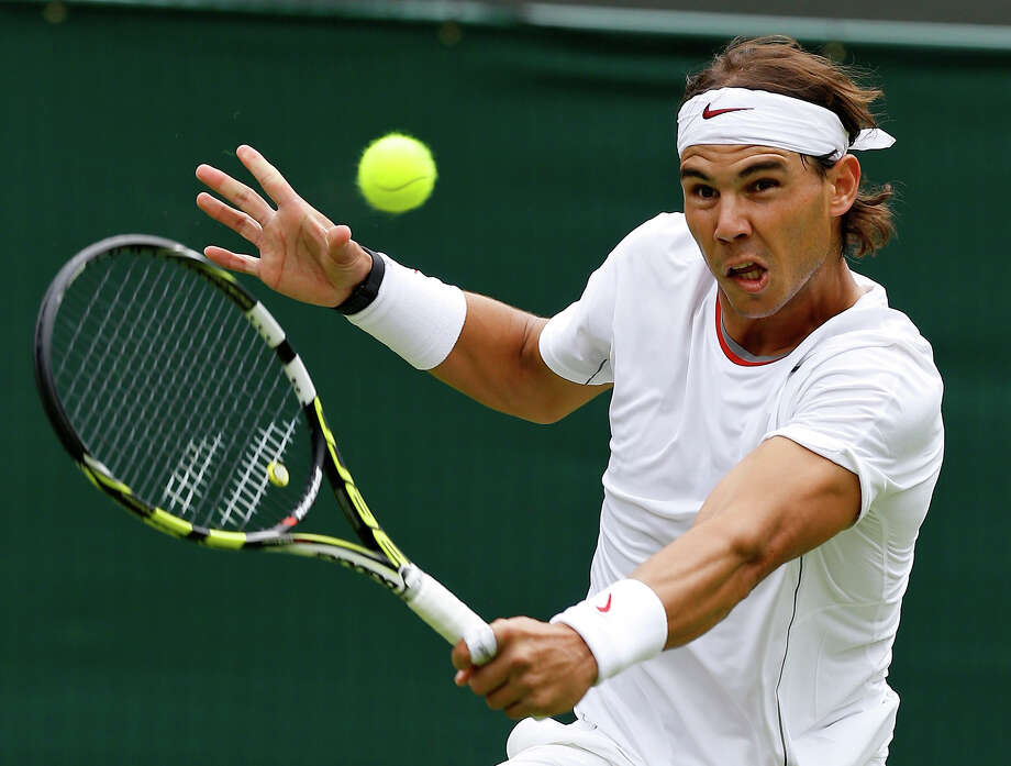 Rafael Nadal of Spain plays a return to Steve Darcis of Belgium during their Men's first round singles match at the All England Lawn Tennis Championships in Wimbledon, London, Monday, June 24, 2013. Photo: Kirsty Wigglesworth, ASSOCIATED PRESS / AP2013