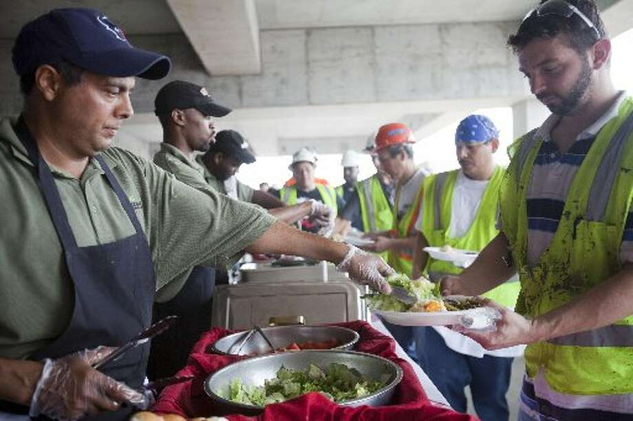 Construction workers enjoy the buffet. Photo: Eric Kayne