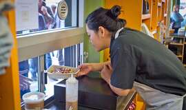 Chef Grace Nguyen hands out boxes for lunch for students from Palo Alto High School at Asian Box in Palo Alto.