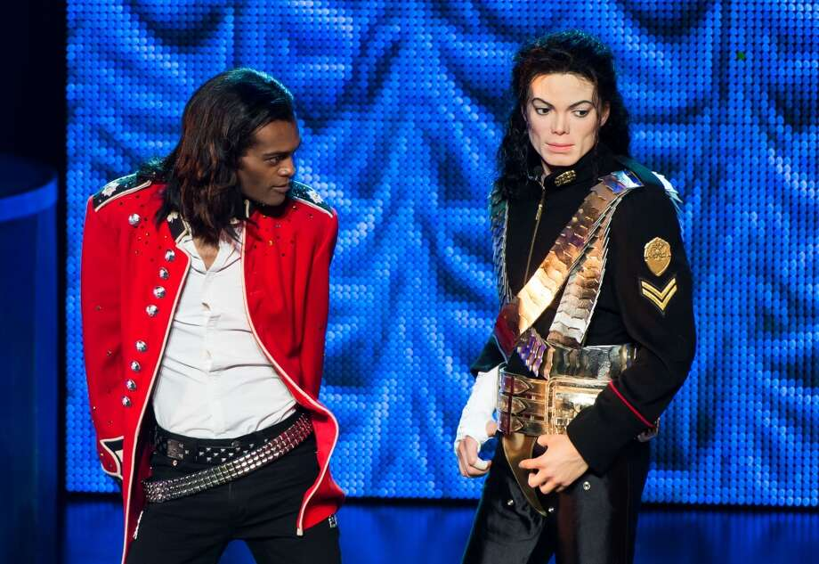 A performer from the 'Thriller Live!' stage show poses on stage with a waxwork figure of Michael Jackson.