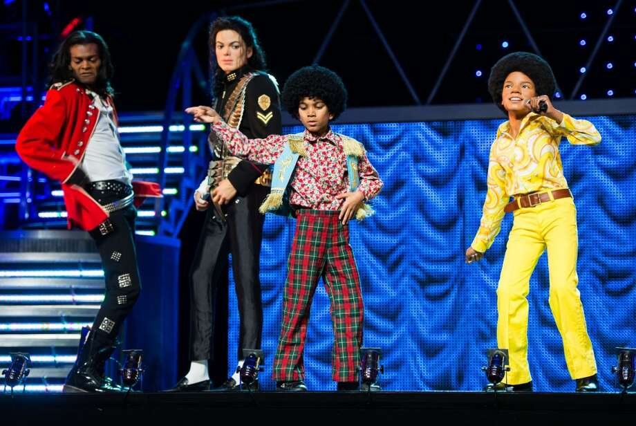 Performers from the 'Thriller Live!' stage show pose on stage with Waxwork figures of Michael Jackson as Madame Tussauds unveil 3 new Michael Jackson waxworks at Lyric Theatre on June 24, 2013 in London, England.