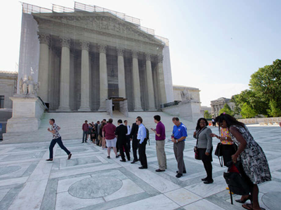 FILE - Visitors wait outside the Supreme Court in Washington on June 20, 2013. The New York Times reported Tuesday the U.S. Justice Department would examine and potentially litigate affirmative action policies at America's schools. Photo: J. Scott Applewhite, AP / AP