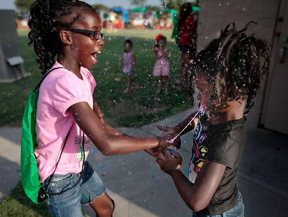 Here, let me show you - it's the least I can do: Ten-year-old Ariana Polk helps her sister, Harmoni, shoot her silly string, which naturally results in Harmoni getting sprayed in the face. The sisters were enjoying the Juneteenth Celebration at Woodson Park in Odessa, Texas. Photo: Ryan Evon, Associated Press