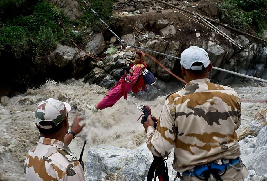 Dangerous crossing: Border police pull a stranded Indian pilgrim across a raging river in Govind Ghat, India. Bad weather hampered rescue operations in northern India where up to 1,000 people are feared dead in landslides and flash floods that have left pilgrims and tourists stranded without food or water. Photo: Manan Vatsyayana, AFP/Getty Images