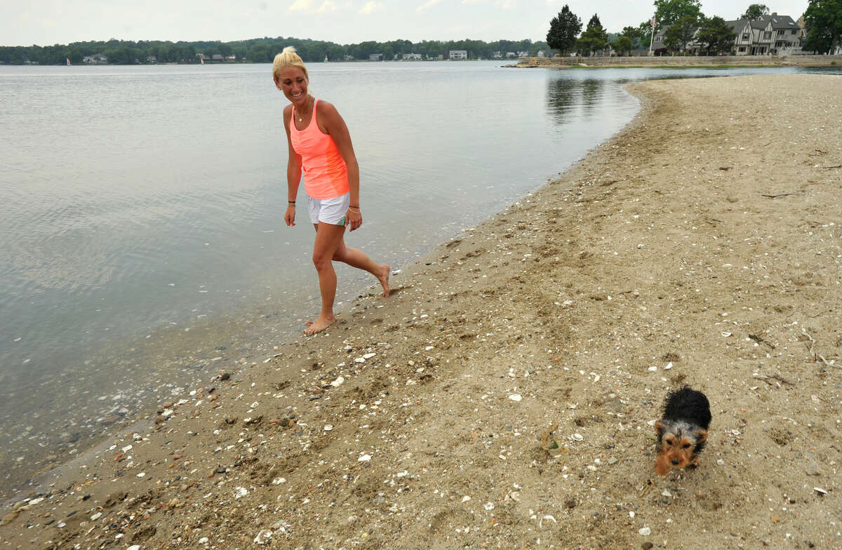 Kyle Roth walks her dog, Winston, on the East end of Cove Island Park on Monday, June 24, 2013. Last Friday afternoon 13-year-old Rashad Gross drowned in the channel between the East end of the park and Brush Island.
