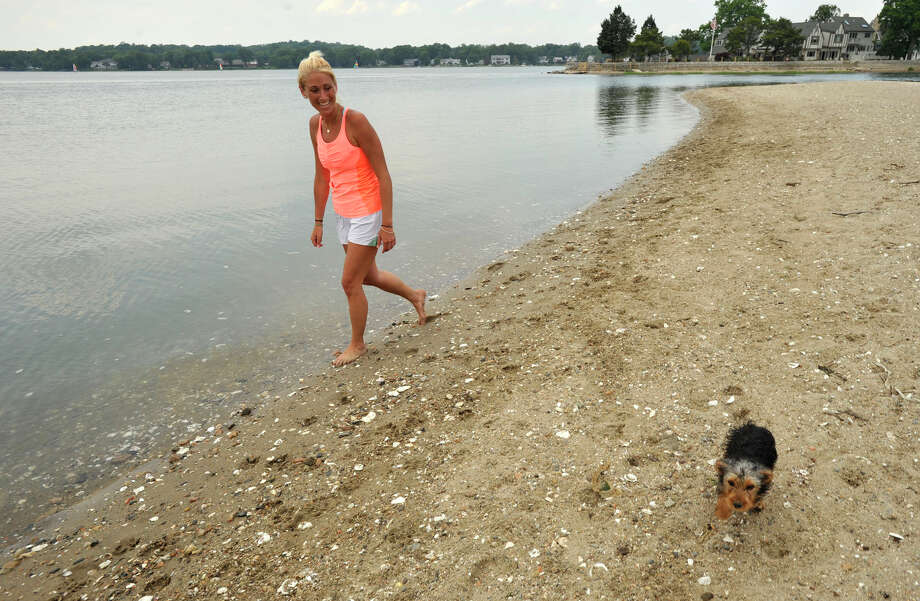Kyle Roth walks her dog, Winston, on the East end of Cove Island Park on Monday, June 24, 2013. Last Friday afternoon 13-year-old Rashad Gross drowned in the channel between the East end of the park and Brush Island. Photo: Jason Rearick / Stamford Advocate