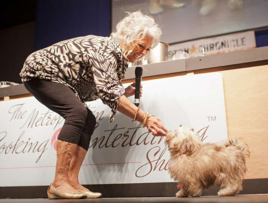Paula Deen gives her dog Lulu, a Havanese , after Lulu did a trick during The Metropolitan Cooking & Entertaining Show, Sunday, Sept. 16, 2012, in Reliant Center in Houston.  ( Nick de la Torre / Houston Chronicle )