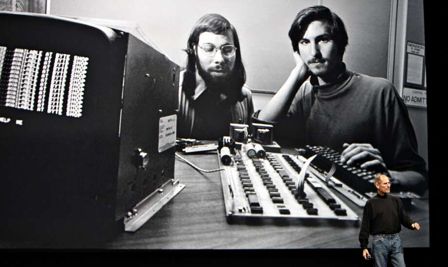 FILE: Steve Jobs, chief executive officer of Apple Inc., right, speaks in front of a file photograph of himself and Apple co-founder Steve Wozniak during the launch of the Apple iPad tablet at the Yerba Buena Center for the Arts Theater in San Francisco, California, U.S., on Wednesday, Jan. 27, 2010. Jobs, who built the world's most valuable technology company by creating devices that changed how people use electronics and revolutionized the computer, music and mobile-phone industries, died Wednesday, Oct. 5, 2011. He was 56. Photographer: Tony Avelar/Bloomberg *** Local Caption *** Steve Jobs