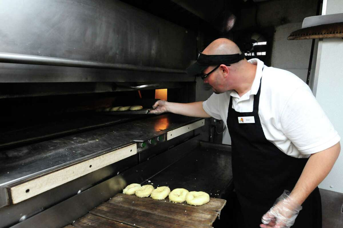 Brian Sheldon puts a tray of bagels into the oven at Bruegger's Bagels on Congress Street Monday, June 24, 2013, in Troy, N.Y. Bruegger's will celebrate its 30th anniversary on Tuesday. The Troy store was the company?s first. (Will Waldron/Times Union)