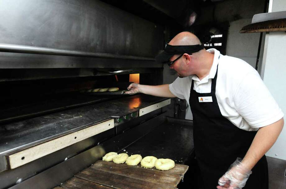 Brian Sheldon puts a tray of bagels into the oven at Bruegger's Bagels on Congress Street Monday, June 24, 2013, in Troy, N.Y. Bruegger's will celebrate its 30th anniversary on Tuesday. The Troy store was the company?s first. (Will Waldron/Times Union) Photo: Will Waldron