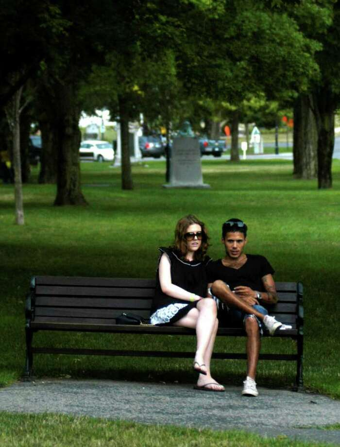 Imogen Armstrong of Trinidad and Tobago and Ryan Jacobs of South Africa, both staffers at Buck's Rock Camp in New Milford, enjoy a relaxing evening together on the Village Green. Photo: Norm Cummings / The News-Times
