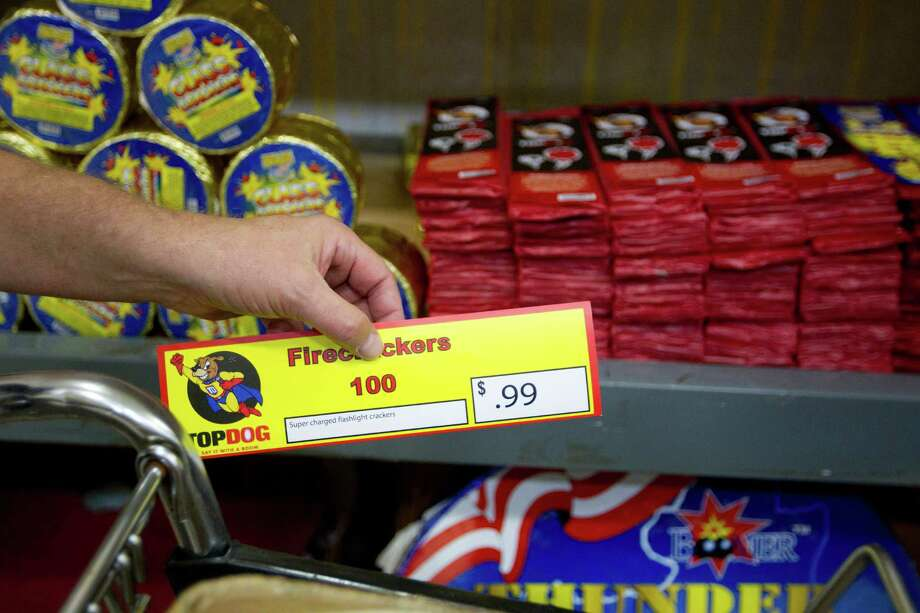 Barry Moseley, a volunteer at Top Dog Fireworks, checks the price on various items while stocking fireworks during the first day of firework sales Monday in Houston. Many student and parent volunteers from Cypress Springs High School work at Top Dog Fireworks as proceeds from the sales go to support the Cypress Springs band and Key Club among other organizations. Photo: Johnny Hanson, Houston Chronicle / © 2013  Houston Chronicle