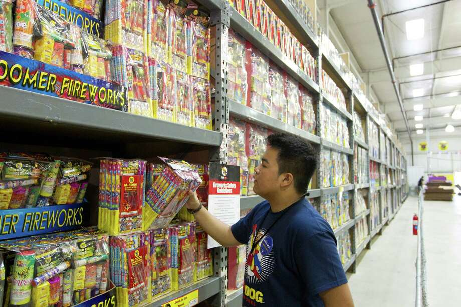Paolo Agcaoili, a senior at Cypress Springs High School volunteers at Top Dog Fireworks, during the first day of firework sales Monday, in Houston. 
