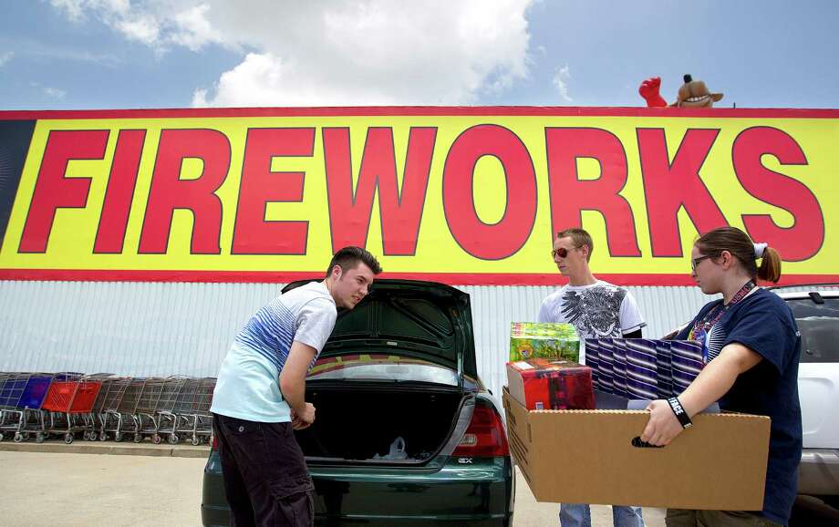 Matt Waller, 21 left, and Devin Yates, 20, are assisted by Ashley Coco, after purchasing fireworks at Top Dog Fireworks during the first day of firework sales Monday, in Houston.  Waller said that they put on a fireworks show for their neighborhood every Fourth of July. Photo: Johnny Hanson, Houston Chronicle / © 2013  Houston Chronicle