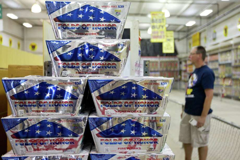 Barry Moseley, a volunteer at Top Dog Fireworks, checks the price on various items next to the Folds of Honor firework, where $10 from each Folds of Honor purchased will go to the Folds of Honor charity stocking fireworks during the first day of firework sales Monday, in Houston. 