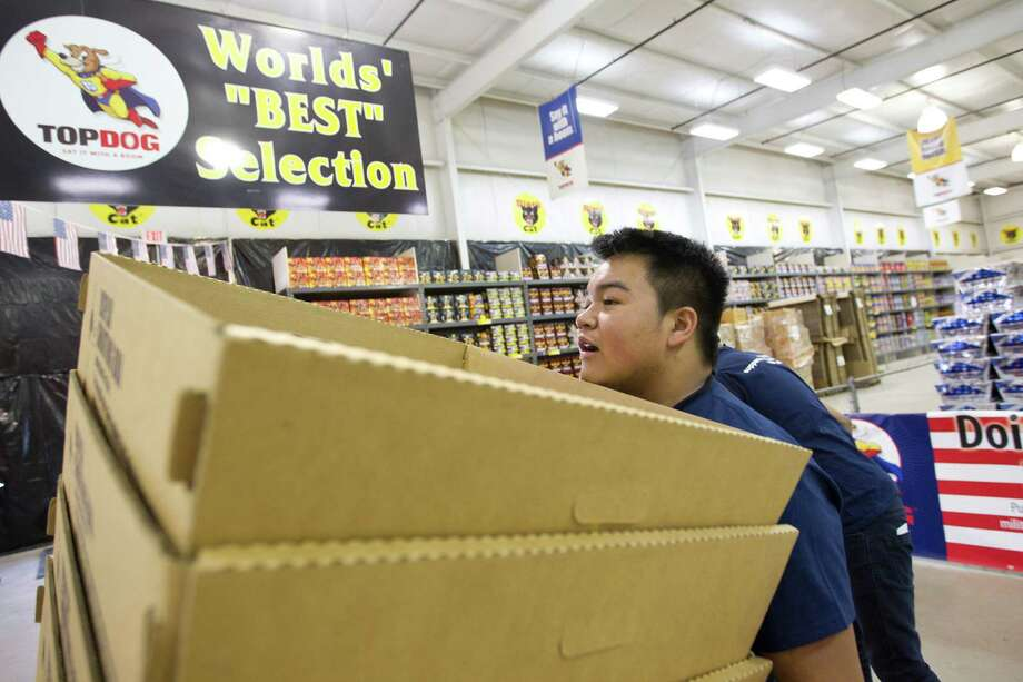 Paolo Agcaoili, a senior at Cypress Springs High School moves boxes while volunteering at Top Dog Fireworks, during the first day of firework sales Monday, in Houston. 