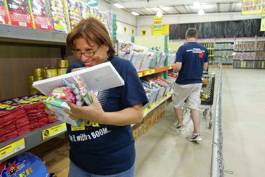Marlene Moseley, a volunteer at Top Dog Fireworks, checks the price on various items while stocking fireworks during the first day of firework sales Monday, in Houston. 