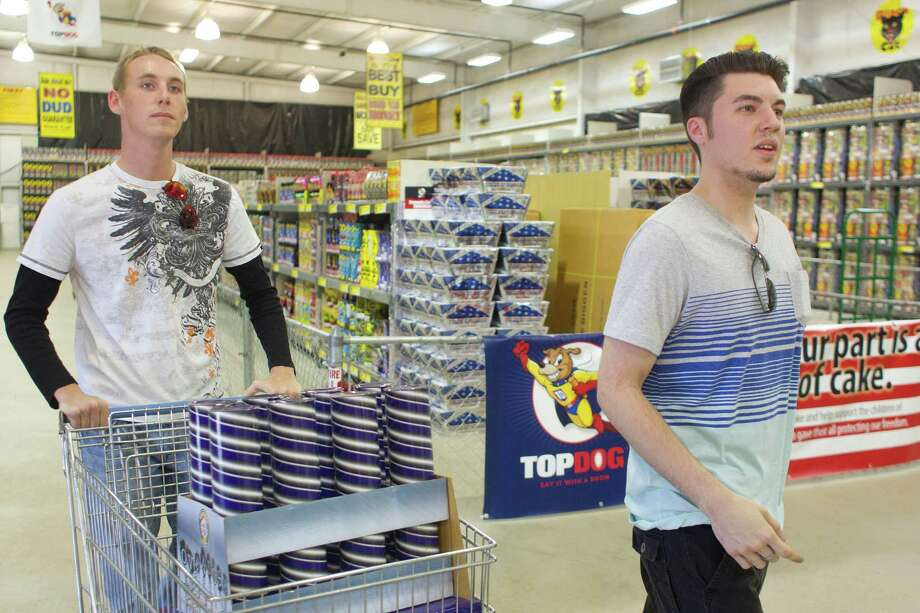 Matt Waller, 21 right, and Devin Yates, 20, purchase fireworks at Top Dog Fireworks during the first day of firework sales Monday, in Houston. 