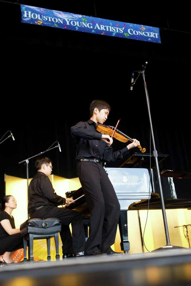 Ethan Le on the violin, and Kevin Le, on the piano, perform Brahms: Hungarian Dance No. 1 during the Houston Young Artists' Concert at Miller Outdoor Theatre in Houston. A second performance scheduled for July 2. Photo: Brett Coomer, Houston Chronicle / © 2013 Houston Chronicle