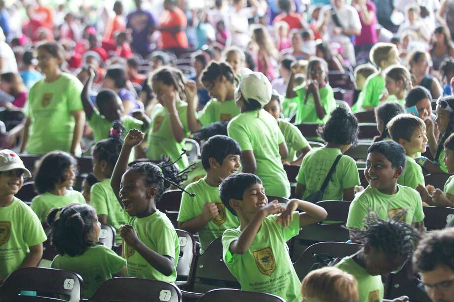 Children in the audience dance during the Houston Young Artists' Concert at Miller Outdoor Theatre in Houston. A second performance scheduled for July 2. Photo: Brett Coomer, Houston Chronicle / © 2013 Houston Chronicle