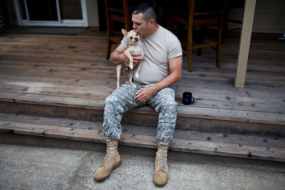 California National Guard Chief Warrant Officer Mario Garcia kisses his dog Russell at his home June 24, 2013 in Sacramento, California. Garcia is an openly gay soldier and will be manning a recruiting booth at the San Francisco Pride festival. Photo: Max Whittaker/Prime, Special To The Chronicle