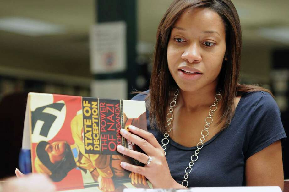 Thea MacFawn a Shaker High teacher, looks through a book on the holocaust which is used in her curriculum Friday, June 21, 2013, at Shaker High School in Colonie, N.Y. MacFawn was selected as a teaching fellow for the United States Holocaust Museum in Washington D.C. for the 2013-14 school year. (Will Waldron/Times Union) Photo: Will Waldron