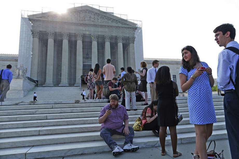 People line up in front of the Supreme Court in Washington, D.C. A court ruling may have put voters in Texas and North Carolina in a difficult situation. (AP Photo/Charles Dharapak) Photo: Charles Dharapak