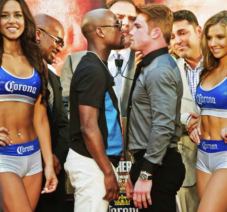 "Floyd Mayweather, center left, poses in a face-off with Saul ""Canelo"" Alvarez during a boxing news conference on Monday, June 24, 2013, at New York's Times Square. MayWeather and Alvarez kicked-off an 11-city promotional, making their fight in Las Vegas in September official. The undefeated fighters announced on Twitter last month that they would face each other at the MGM Grand on Sept. 14. (AP Photo/Bebeto Matthews) Photo: Bebeto Matthews"