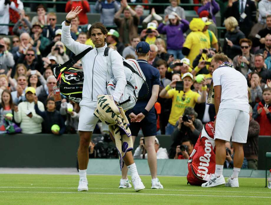 Rafael Nadal of Spain, left, waves to spectators after losing to Steve Darcis of Belgium, right, in their Men's first round singles match at the All England Lawn Tennis Championships in Wimbledon, London, Monday, June 24, 2013. (AP Photo/Kirsty Wigglesworth) Photo: Kirsty Wigglesworth