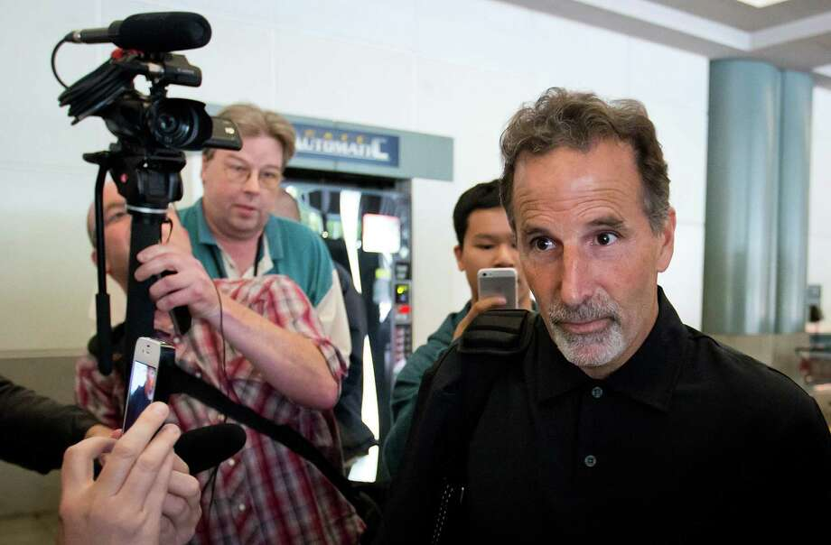 Former New York Rangers hockey coach John Tortorella, center, walks out a side door to a waiting vehicle after arriving at Vancouver International Airport in Richmond, British Columbia, on Friday June 21, 2013.(AP Photo/The Canadian Press, Darryl Dyck) Photo: Darryl Dyck