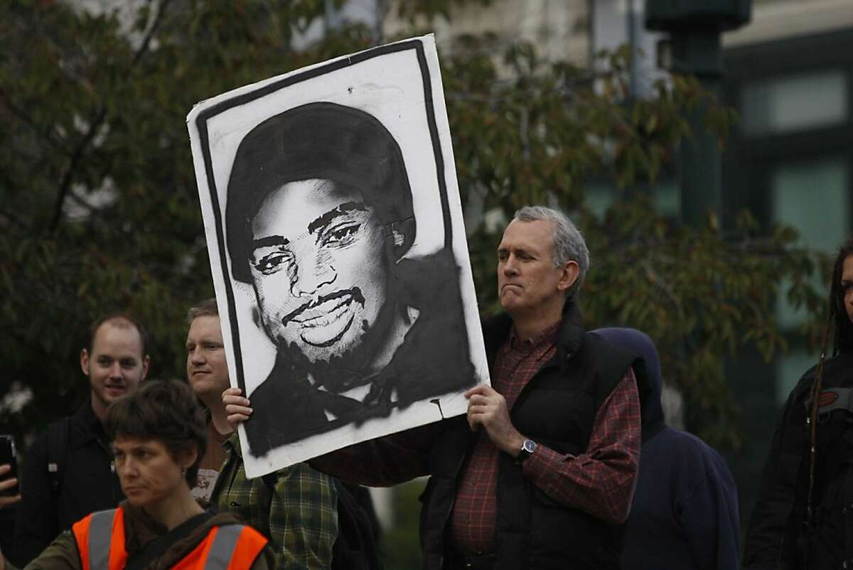 Dave Pugh holds a painting of Oscar Grant in front of City Hall during a peaceful rally in staged in response to a two year prison sentence that was handed down to former BART officer Johannes Mehserle on Friday Nov. 05, 2010 in Oakland, Calif.