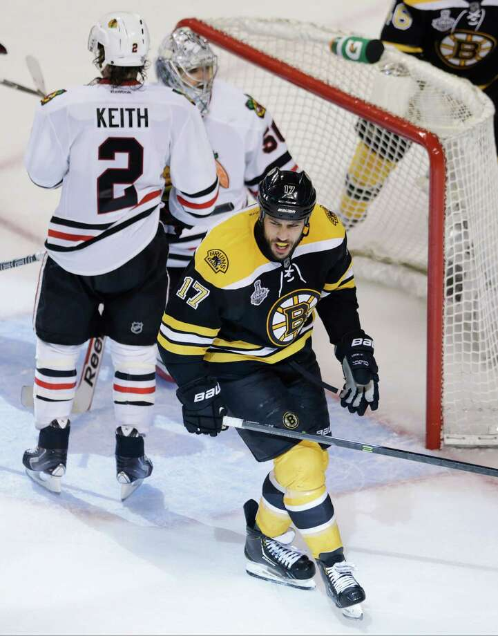 Boston Bruins left wing Milan Lucic, foreground, reacts after scoring past Chicago Blackhawks defenseman Duncan Keith (2) and goalie Corey Crawford, right, during the third period in Game 6 of the NHL hockey Stanley Cup Finals, Monday, June 24, 2013, in Boston. (AP Photo/Charles Krupa) Photo: Charles Krupa, Associated Press / AP