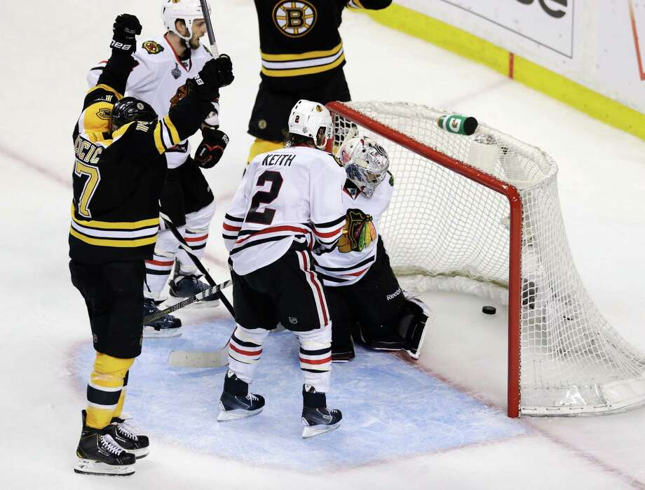 Boston Bruins left wing Milan Lucic, left, reacts after scoring past Chicago Blackhawks defenseman Duncan Keith (2) and goalie Corey Crawford, hidden during the third period in Game 6 of the NHL hockey Stanley Cup Finals, Monday, June 24, 2013, in Boston. (AP Photo/Charles Krupa) Photo: Charles Krupa, Associated Press / AP