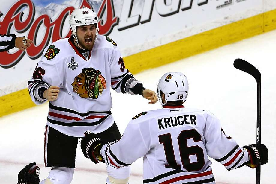 The Blackhawks' Dave Bolland (left) dropped his gloves in celebration after scoring the go-ahead goal late in the third period of Game 6 in Boston. At right is teammate Marcus Kruger. Photo: Elsa, Getty Images