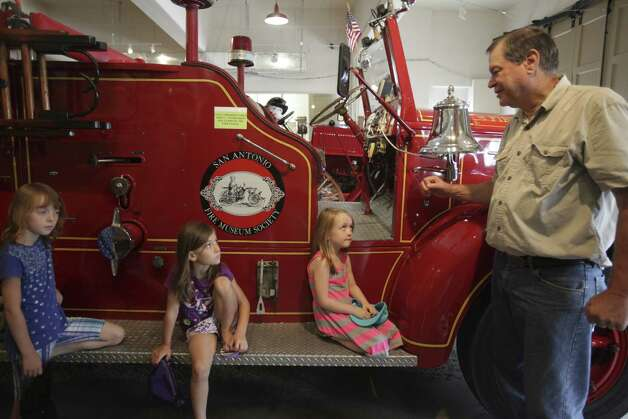 Al Michalczak, who worked for the Fire Department for 33 years, talks to sisters Taylor, 8, Lainey, 6, and Sophia Sloan, 5. Photo: Abbey Oldham / San Antonio Express-News