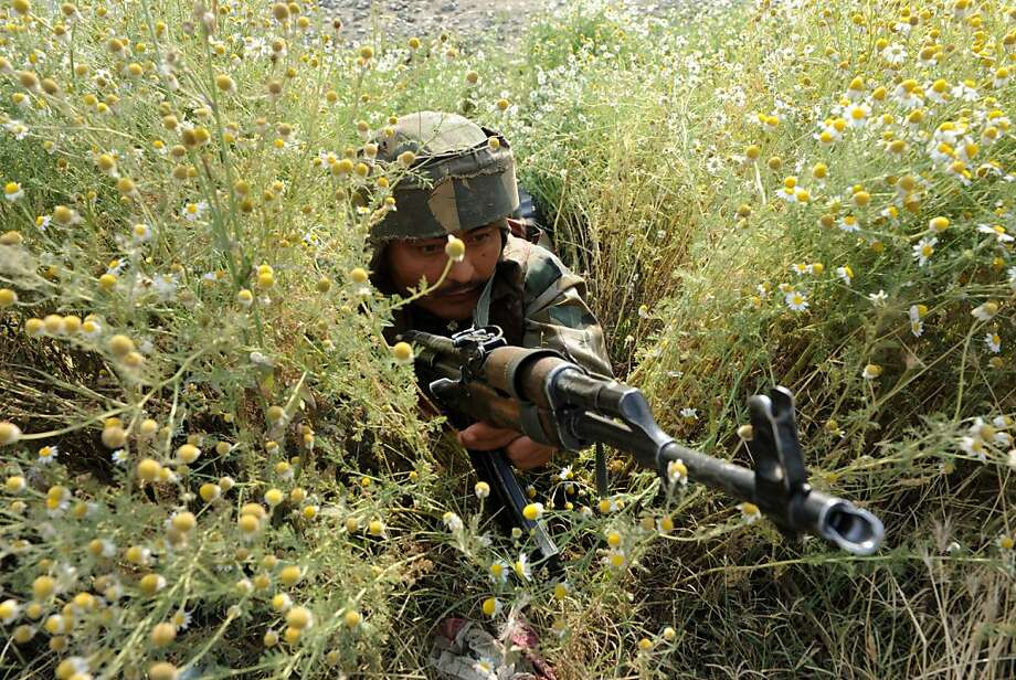 TOPSHOTS An Indian army soldier takes position at the scene of a deadly attack by armed rebels on the outskirts of Srinagar on June 24, 2013. Four soldiers were killed and six others were wounded in an attack on a convoy in Indian Kashmir on the eve of a visit by Prime Minister Manmohan Singh, the army said.  AFP PHOTO/ Rouf BHATROUF BHAT/AFP/Getty Images Photo: Rouf Bhat, AFP/Getty Images
