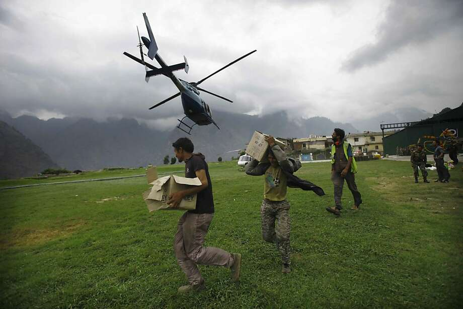 Indian civilians get ready to load relief material for flood affected victims on a helicopter at a makeshift helipad at Joshimath, in northern Indian state of Uttarakhand, Monday, June 24, 2013. A top official said the death toll in northern India could rise as army soldiers clear the debris from towns and villages flattened by landslides and monsoon flooding.Home Minister Sushilkumar Shinde said the number of people who have perished in the floods that washed away thousands of homes could go beyond the 1,000 deaths reported so far (AP Photo/Rafiq Maqbool) Photo: Rafiq Maqbool, Associated Press
