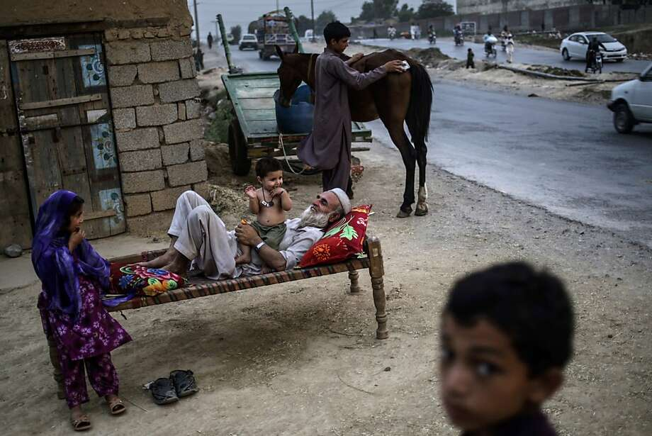 Pakistani Abdulrahman Qassim, 62, lies on a bed outside his home playing with his one-year-old grandson Abdulaziz, and his granddaughter Zulikha, 6, left, on the outskirts of Islamabad, Pakistan, Monday, June 24, 2013.  Abdulrahman and his family fled their home from Pakistan's tribal region of Mohmand Agency, due to fighting between the Taliban and the army, and took refuge in Islamabad. (AP Photo/Muhammed Muheisen) Photo: Muhammed Muheisen, Associated Press