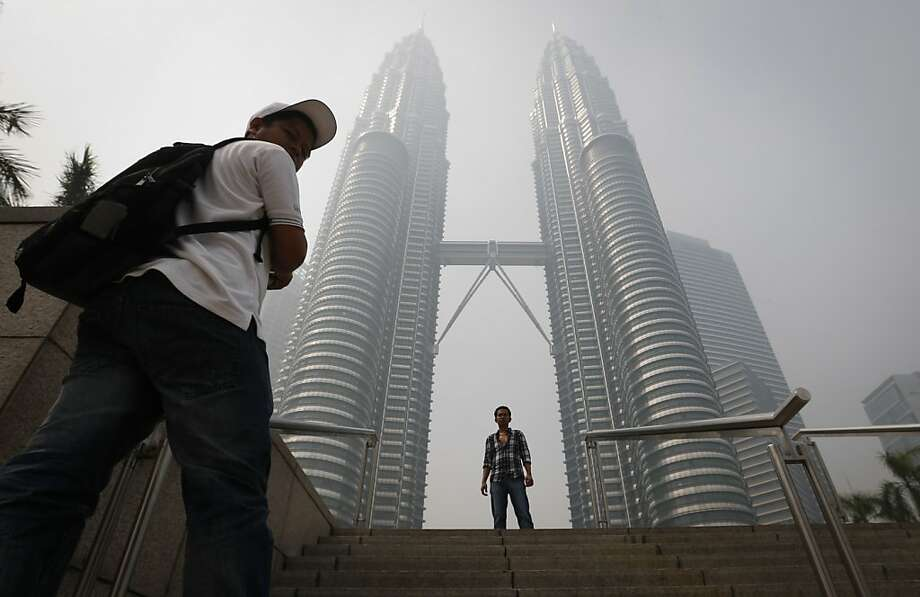 A tourist poses for a photo in front of  Malaysia's landmark Petronas Twin Towers obscured in haze in Kuala Lumpur, Malaysia, Monday, June 24, 2013. Malaysian authorities declared a state of emergency Sunday in a southern district where a smoky haze blamed on Indonesian forest fires has triggered one of the country's worst pollution levels in years. (AP Photo/Vincent Thian) Photo: Vincent Thian, Associated Press