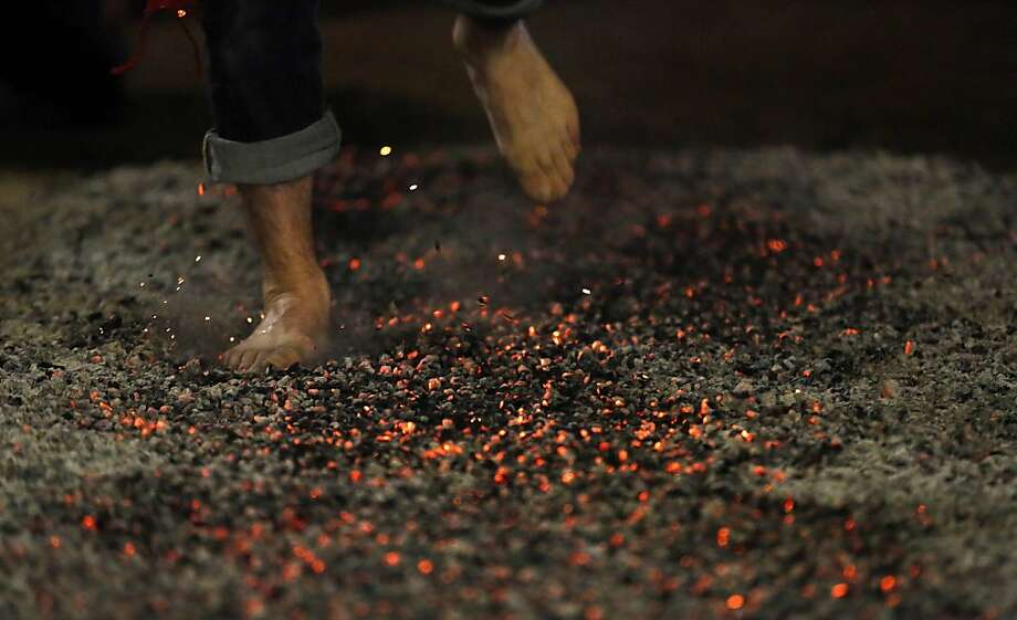 A reveler rushes through burning embers during the night of San Juan in San Pedro Manrique, Soria province in northern Spain early on June 24, 2013. The ritual consists in starting a bonfire and for the locals to step barefoot on hot coals without burning the soles of their feet, and most times with someone on their back. TOPSHOTS    AFP PHOTO/CESAR MANSOCESAR MANSO/AFP/Getty Images Photo: Cesar Manso, AFP/Getty Images