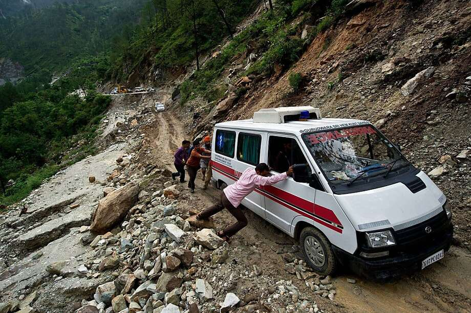 Indian people push an ambulance through a damaged section of the road caused by overnight rains in Gauchar on June 24, 2013.  Indian priests are planning to cremate hundreds of flood victims on June 24, as heavy rains halted the search for thousands of tourists stranded in the devastated Himalayan region, officials said.   TOPSHOTS    AFP PHOTO/MANAN VATSYAYANAMANAN VATSYAYANA/AFP/Getty Images Photo: Manan Vatsyayana, AFP/Getty Images