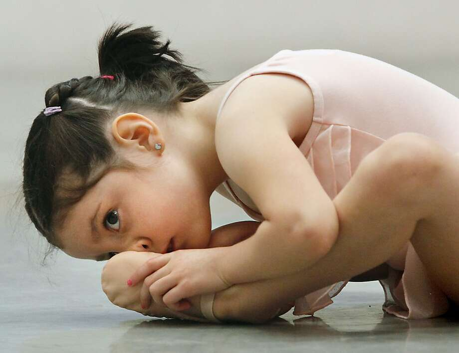 Esther Draney, 4, of Richland, stretches on Monday during an Angelina Ballerina summer camp session at the Tri-Cities Academy of Ballet & Music in Richland, Wash., Monday, June 24, 2013. The camp is one of many summer activities in the Tri-Cities. (AP Photo/Tri-City Herald, Kai-Huei Yau) Photo: Kai-Huei Yau, Associated Press