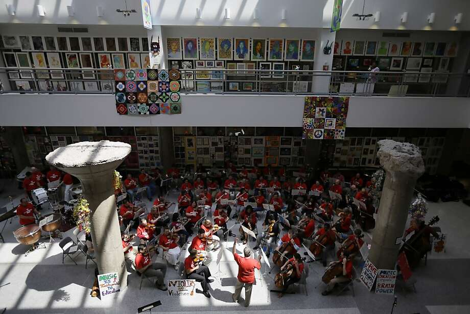 Conductor William Scheible directs a farewell concert with music teachers slated to loose their jobs and former students, at the Philadelphia school district's headquarters, Monday, June 24, 2013, in Philadelphia. Education advocates are doing everything they can to draw attention to the dire situation in the city's public schools, which are facing a $304 million deficit. To cover the gap, the district has laid off 20 percent of its staff. More than 3,800 employees will be jobless next week, from assistant principals to secretaries. (AP Photo/Matt Slocum) Photo: Matt Slocum, Associated Press