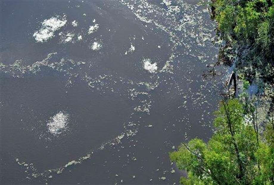 In this photo taken Tuesday, Aug. 7, 2012, bubbles come to the surface where pipelines cross Bayou Corne near Pierre Part, La. A pipeline sign is seen at  right. State officials said small amounts of diesel hydrocarbons were found in swamp water where an acre of swampland had liquefied over one weekend, while experts tried to determine whether the occurrence was natural or caused by human activity. Texas Brine Co. LLC facility, is seen at top left; a well pad for a plugged and abandoned salt cavern is at top right. Photo: Bill Feig, AP / The Baton Rouge Advocate