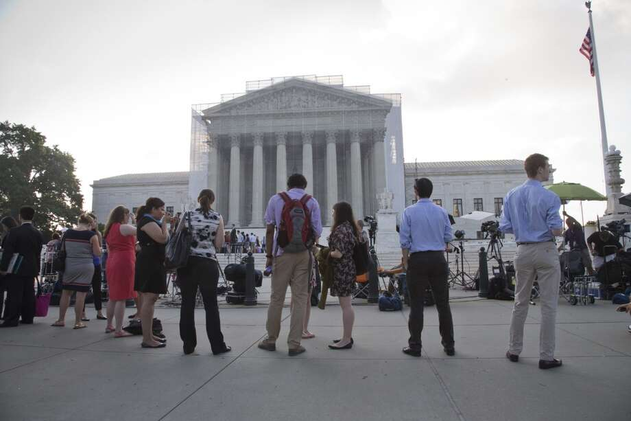 People wait outside the Supreme Court in Washington as key decisions are expected to be announced Monday, June 24, 2013. At the end of the court's term, several major cases are still outstanding that could have widespread political impact on same-sex marriage, voting rights, and affirmative action. (AP Photo/J. Scott Applewhite) Photo: J. Scott Applewhite, Associated Press