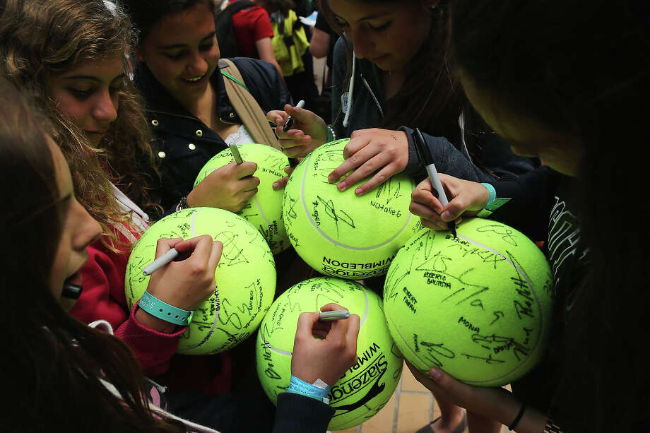 Young tennis fans write the names of players next to their autographs on giant tennis balls during day two of the Wimbledon Lawn Tennis Championships at the All England Lawn Tennis and Croquet Club on June 25, 2013 in London. Photo: Dan Kitwood, Getty Images / 2013 Getty Images