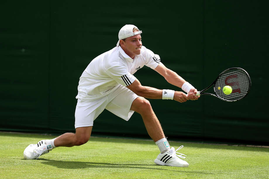 James Duckworth of Australia plays a backhand during his Gentlemen's Singles first wround match against Denis Kudla of the United States of America on day two of the Wimbledon Lawn Tennis Championships at the All England Lawn Tennis and Croquet Club on June 25, 2013 in London. Photo: Clive Brunskill, Getty Images / 2013 Getty Images