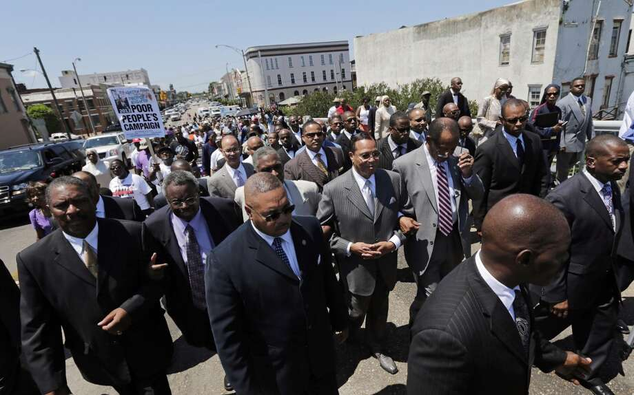 Nation of Islam Leader Louis Farrakhan (at center with hands clasped) joins others in a march across the historic Edmund Pettus Bridge in Selma, Ala., on a voting rights caravan across Alabama on Friday, June 14, 2013. Farrakhan spoke at rallies earlier Friday in Birmingham and in Shelby County. (AP Photo/Dave Martin)