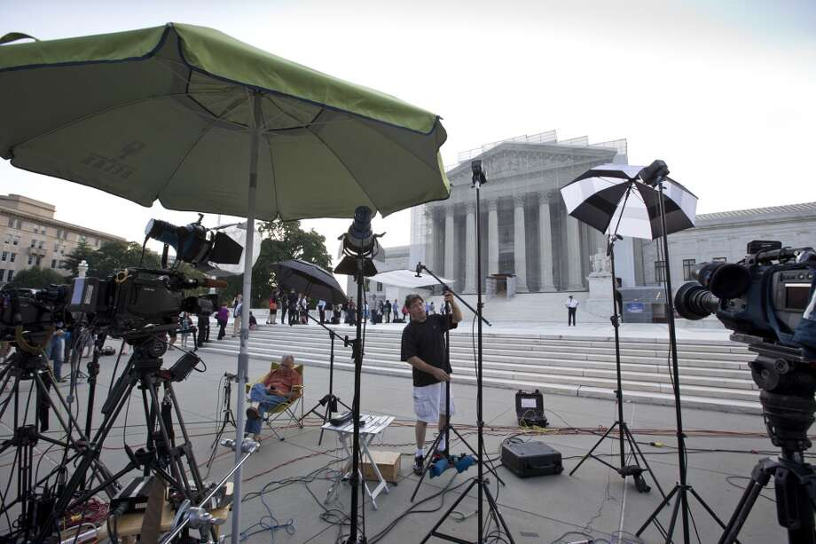 TV crews wait outside the Supreme Court in Washington as key decisions are expected to be announced Monday, June 24, 2013. At the end of the court's term, several major cases are still outstanding that could have widespread political impact on same-sex marriage, voting rights, and affirmative action. (AP Photo/J. Scott Applewhite)
